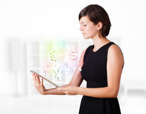 Women looking at tablet with currency icons. Young business woman looking at modern tablet with currency icons Royalty Free Stock Photos