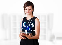 Women looking at tablet with currency icons. Young business woman looking at modern tablet with currency icons Royalty Free Stock Images