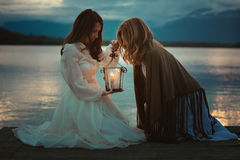 Women looking into warm light lantern Royalty Free Stock Photography