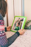 A woman looks at a photo. A women looks at a photo of a boy. Mom holds a photo frame with a photograph of her son. A small child and memories Stock Photo