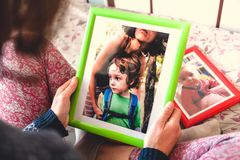 A woman looks at a photo. A women looks at a photo of a boy. Mom holds a photo frame with a photograph of her son. A small child and memories Royalty Free Stock Photography