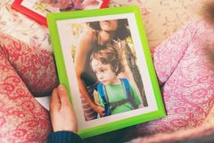 A woman looks at a photo. A women looks at a photo of a boy. Mom holds a photo frame with a photograph of her son. A small child and memories Stock Photos