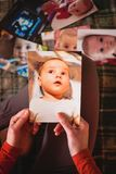 Photos of a small child. A women looks at the pictures of a small child. Mom remembers her son`s childhood. Moments of life of a newborn baby Royalty Free Stock Image
