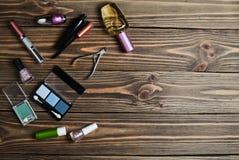 Women& x27; los cosméticos de s para el maquillaje, los objetos para el cuidado de clavos y los perfumes mienten en una tabla de  Imagen de archivo
