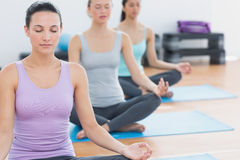 Women in lotus posture with eyes closed at fitness studio Royalty Free Stock Images