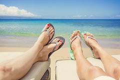 Women Lounging and sunbathing on an idyllic beach. Sandy toes and feet of two women relaxing on chaise lounge chairs while enjoying a tranquil beach vacation Royalty Free Stock Photo