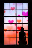 Women in love looking through big window the hearts in the sky Royalty Free Stock Photos