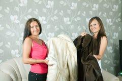 Women  make boast of fur coats. In home Stock Photos