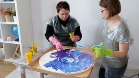 Women making fluid art acrylic painting. Creative cosmic artwork hippie wallpaper in blue color with hands of creator. Women make fluid artwork. Fluid art stock video footage