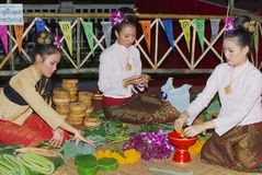 Women make Krathong flower bowls with banana leaves during Loi Krathong celebration at ningt in Chiang Mai, Thailand. Stock Photography