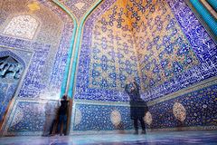 Women make photo pictures in blue and yellow colors mosque with tiles on walls in Middle East. Royalty Free Stock Photo