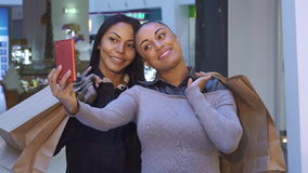 Women make selfie with shopping bags. Two beautiful women making selfie with shopping bags. Young african american girls photographing themselves at the mall stock footage