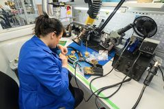 Free Women Make Soldering Of Radio Components To Electronic Boards. Plant For The Production Of Electronic Equipment. Stock Photography - 109716092