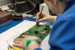 Free Women Make Soldering Of Radio Components To Electronic Boards. Plant For The Production Of Electronic Equipment. Royalty Free Stock Photo - 116060555