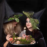 Women make up as witches eating mushrooms. Women make up as witches for Halloween, in the studio Stock Photos