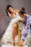 Women making adjustment in designer studio. Women making adjustment to wedding gown in professional fashion designer studio stock images