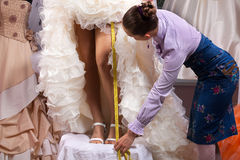 Women making adjustment in designer studio. Women making adjustment to wedding gown in professional fashion designer studio royalty free stock photo