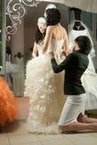 Women making adjustment to wedding gown
