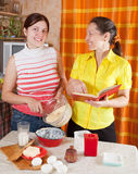 Women making Easter cake with  cookbook Royalty Free Stock Photography
