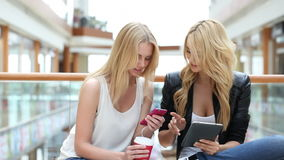 Women in mall using smartphone. Young women in shopping mall using digital tablet and smartphone stock video footage