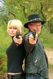 Women and man back-to-back aiming handguns stock image