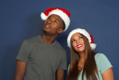 Women man looking up christmas red hat santa claus december holiday party young couple. Christmas men and women wearing santa claus red hat staring up and Royalty Free Stock Photos