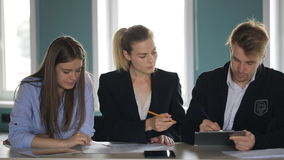 Women and a man sitting in a row at one table and conduct a business meeting. At a long table colleagues of same office and participate in planning of work stock video