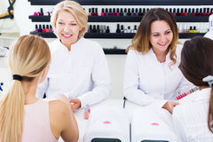 Women manicurists manicuring female clients. Two women manicurists manicuring female clients in nail salon stock images