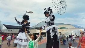 Women in masquerade suits on stilts entertain visitors stock video footage