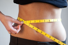 Women measuring waist. Available light shot Royalty Free Stock Photo