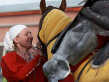 Women in medieval clothes prepares a horse for jousting. St. Petersburg, Russia - July 9, 2017: Women in medieval clothes prepares a horse for jousting during Royalty Free Stock Images