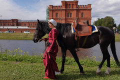 Women in medieval clothes prepares a horse for jousting. St. Petersburg, Russia - July 8, 2017: Women in medieval clothes prepares a horse for jousting during Royalty Free Stock Images