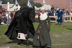 Women in medieval clothes prepares a horse for jousting. St. Petersburg, Russia - July 9, 2017: Women in medieval clothes prepares a horse for jousting during Stock Photography