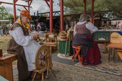 Women with medieval costumes working with fabric Royalty Free Stock Photos