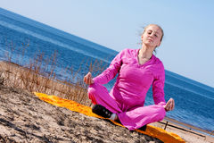 Women meditating on the beach Royalty Free Stock Images