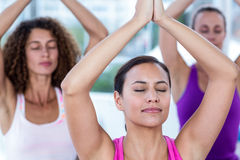 Women meditating with joined hands and arms raised Royalty Free Stock Images