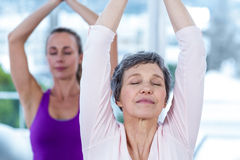 Women meditating with joined hands and eyes closed Royalty Free Stock Images