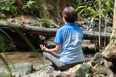 Women meditating by the river Stock Images