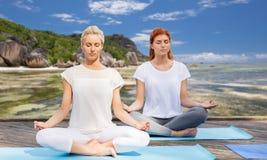Women meditating in yoga lotus pose outdoors Royalty Free Stock Photos