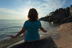 Women meditating in yoga pose on the beach at sunrise. Woman meditating and relaxing in yoga pose towards the sun at peaceful beach sunrise during your holiday Royalty Free Stock Photography