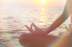 Women  meditating in yoga position on the beach  at sunset close up. Light leaks film camera effect Stock Image