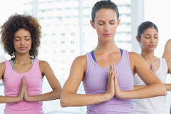 Women in meditation pose with eyes closed at fitness studio Stock Images