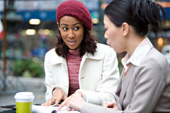 Women Meeting for Business. Two business women having a casual meeting or discussion in the city. Shallow depth of field Royalty Free Stock Images