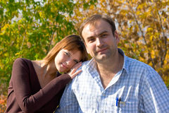 Women and men. The beautiful girl and the young men in autumn park Stock Photography