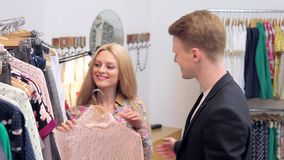 Women and men choose women`s clothes in the store. Young adults couple in good mood shopping at the clothing store. Lifestyle concept stock video footage