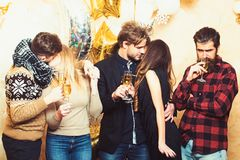 Women and men enjoy party celebration. Friends celebrate christmas or new year. Men and women drink champagne. Couples. Of lovers kiss, relations. Christmas and royalty free stock images