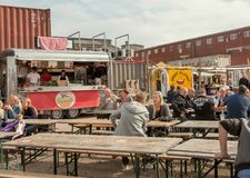 Women and men having fun and eating fast food at street market Reffen, urban area for start-ups stock photo