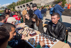 Women and men playing chess on competition at annual autumn city festival of Georgia Royalty Free Stock Photo