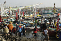 Women and men standing and waiting for the fishing boats Stock Photo