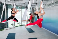 Women and men stretching their backs while trying aerial yoga. Stretching backs. Two active fit women and men stretching their backs while trying aerial yoga stock photography